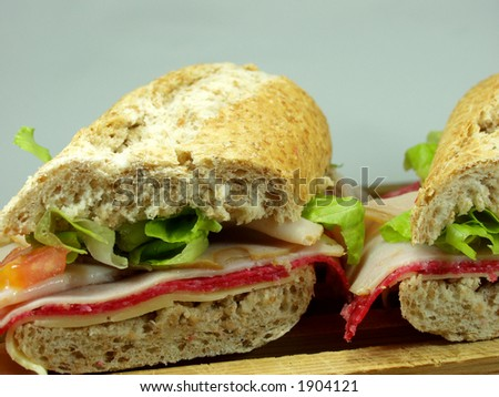 two middle salami sandwich on wooden surface