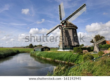 Two mills, large and small, near the river, the Dutch landscape.