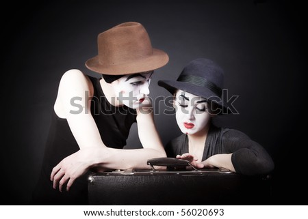 Two mimes man and  woman in hats with a suitcase on  black background - stock photo