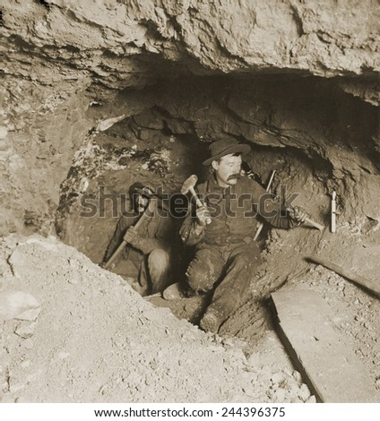 Two miners taking out ore in tunnel of gold mine at Eagle River Canyon, Colorado. C. 1905. - stock photo
