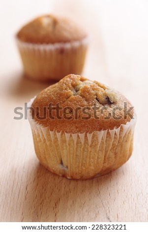 Two mini blueberry muffins on a wooden background - stock photo