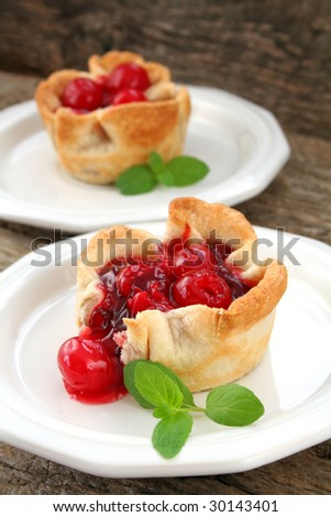 Two mini cherry pies/tarts on white plates garnished with mint leaves. - stock photo