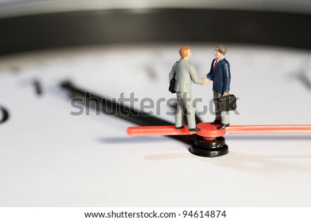 Two miniature businessmen toy models shake hands to seal a business deal while balanced on the hands of a clock, macro side view - stock photo