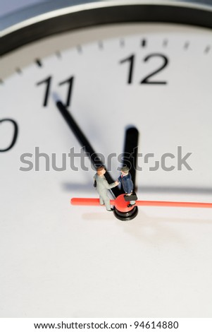 Two miniature businessmen toy models shake hands to seal a business deal while balanced on the hands of a clock, overhead view - stock photo