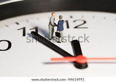 Two miniature businessmen toy models shake hands to seal a business deal while standing on the face of a clock alongside the hands. - stock photo