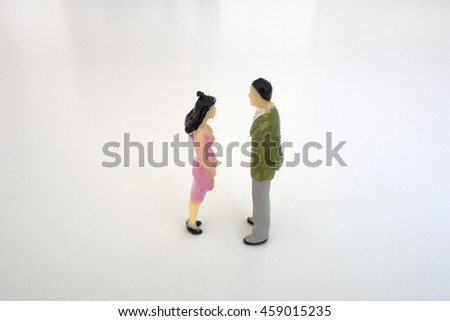 Two miniature figures, a couple: a man and a woman looking at each other