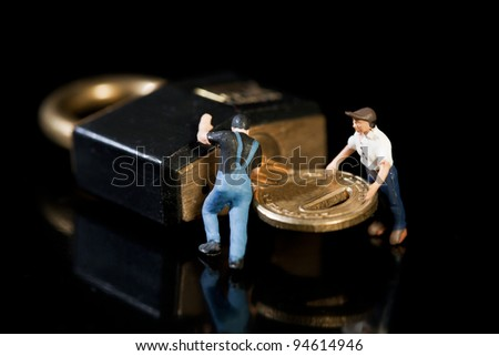 Two miniature figures of workmen turning a key in a padlock to check up on security on a dark background - stock photo