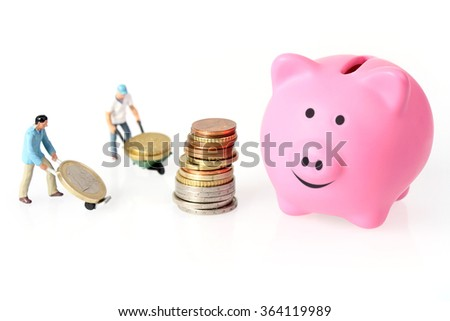 Two Miniature workers drives euro coins in wheelbarrow and piggy bank - stock photo