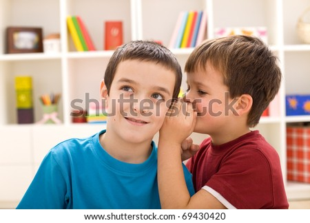 Two mischievous boys sharing a secret - closeup - stock photo