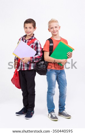 Two mischievous cheerful schoolboy with books in their hands and backpacks on a white background laughing - stock photo