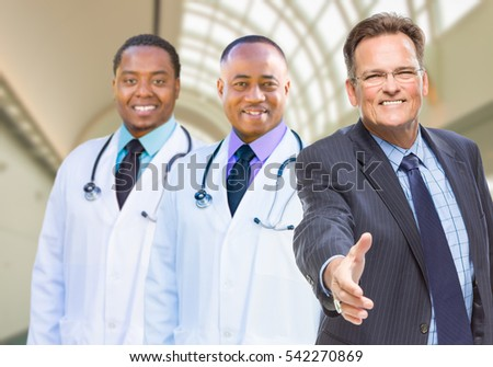 Two Mixed Race Doctors Behind Businessman Reaching for a Hand Shake Inside Hospital.