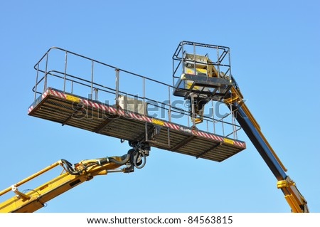 Two mobile platforms elevated towards a blue sky - stock photo