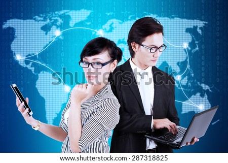 Two modern businesspeople using laptop and smartphone to communicate with their partners in the world - stock photo