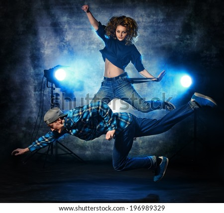 Two modern dancers jumping over grunge background. Hip-hop. Urban, disco style. - stock photo