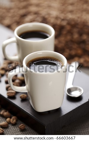two modern espresso cups on a wooden table - stock photo