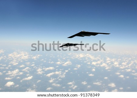 Two modern stealth bombers flying at high speed - stock photo