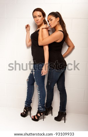 Two modern stylish sexy women friends posing in tight fitting jeans and stilettos close together - stock photo