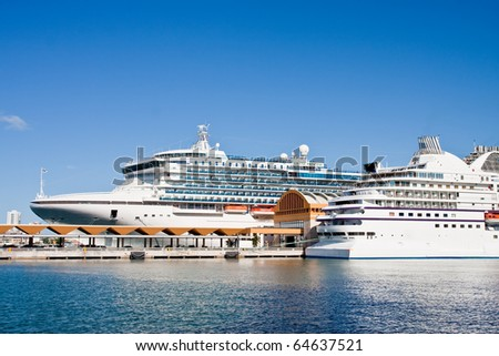 Two modern white cruise ships at a harbor on calm blue water - stock photo