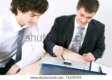 Two modern young businessmen discuss the document - stock photo