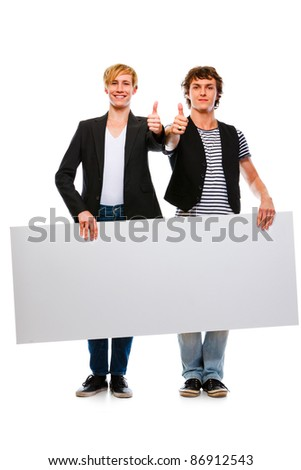 Two modern young men holding blank billboard and showing thumbs up - stock photo