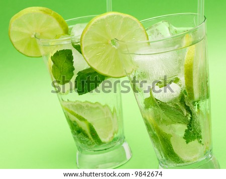 Two mojito cocktails with lime, mint leaves and ice on green background - stock photo
