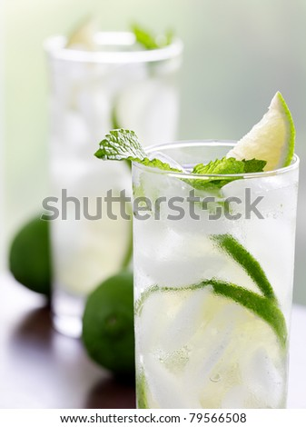 two mojitos closeup with selective focus on mint leaf - stock photo