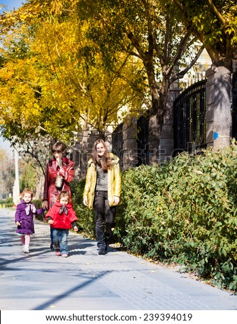 Two mom and two daughters walk in the rays of the autumn sun - stock photo
