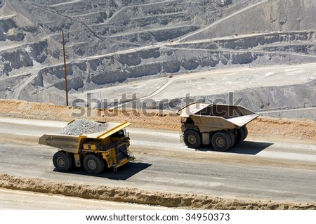 Two monster dump trucks pass each other in an open pit mine. - stock photo