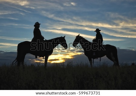 Two Montana cowboys on horseback at silhouetted against dawn sky
