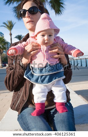 two month age baby red, blue and white clothes open eyes funny expression face standing on legs holding in hands of brunette woman mother with brown jacket sitting in street outdoor - stock photo