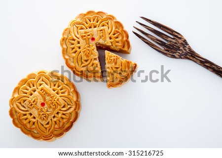 Two moon cake with one cut up and wooden fork for the chinese Mid-Autumn festival on white background - stock photo