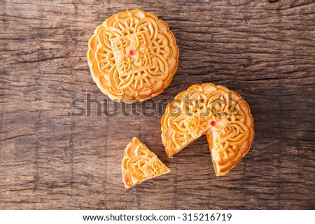 Two moon cake with one cut up for the chinese Mid-Autumn festival on wooden table top - stock photo