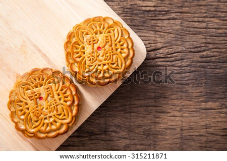 Two moon cake with one cut up to show egg yolk for the chinese Mid-Autumn festival on wooden table top and wooden background - stock photo