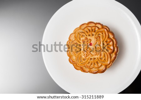 Two moon cake with one cut up to show egg yolk for the chinese Mid-Autumn festival on wooden table top and wooden background