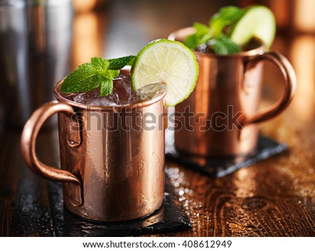 two Moscow mules in copper cup with lime and mint garnish - stock photo