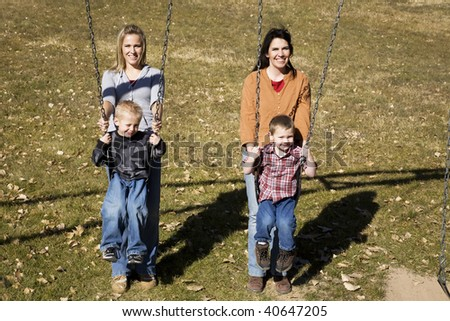 Two mothers pushing their son's on the swings at the park. - stock photo