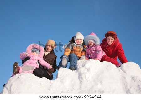 two mothers with child sit on snow hill - stock photo
