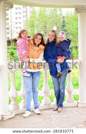 Two mothers with children on the walk in the gazebo - stock photo