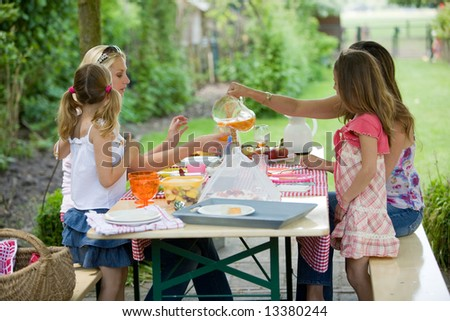 Two mothers with their daughters enjoying an outdoors picnic - stock photo