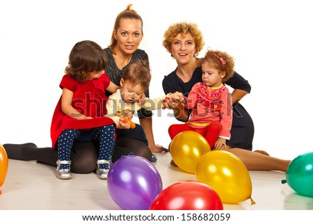 Two mothers with their kids at party with balloons sitting on floor together - stock photo