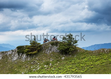 Two motor cross riders on top of the mountain under the cloudy sky - stock photo