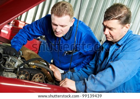 two motor mechanic engineers examining timing belt and internal combustion engine of automobile car at repair service station - stock photo