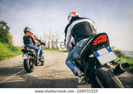 Two motorbikes driving in the nature - Friends driving racing motorcycles with their girlfriends - Three friends riding sport bikes on a week-end tour - stock photo