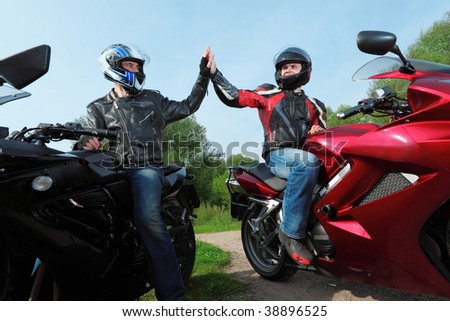 two motorcyclists greetings on country road - stock photo