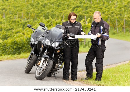 Two motorcyclists studying the Road map - stock photo