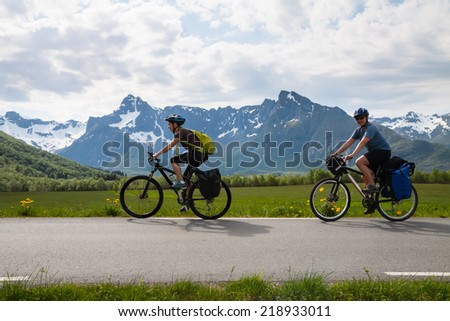 Two mountain bike cyclists at sphalt road, Lofoten, Norway - stock photo