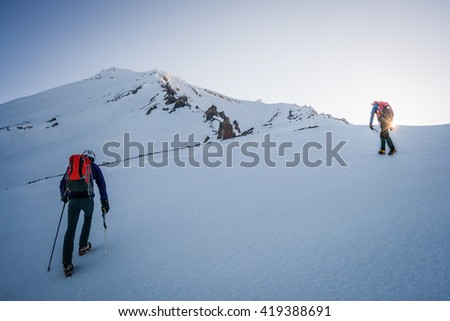 Two mountaineers climbing snowy mountain at dawn.