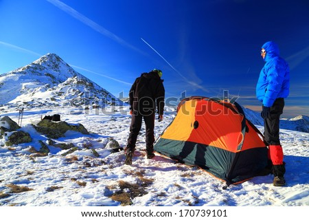 Two mountaineers pitching a tent on snowy mountain