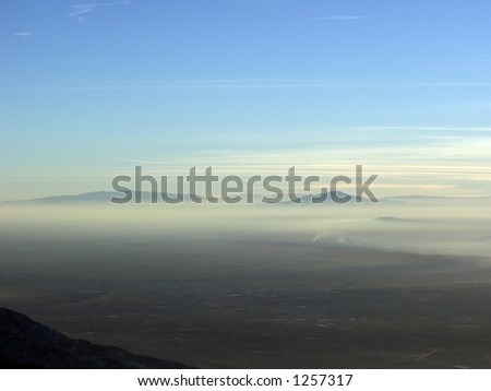 Two mountains poke above the New Mexico desert haze with whispy clouds in the blue sky above.  Just below the right mountain, you can see smoke from a burning fire. - stock photo