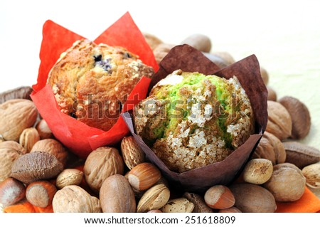 two muffins and nuts on napkin on table - stock photo